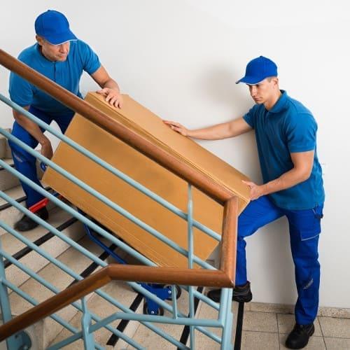 Грузчики поднимают груз на этаж